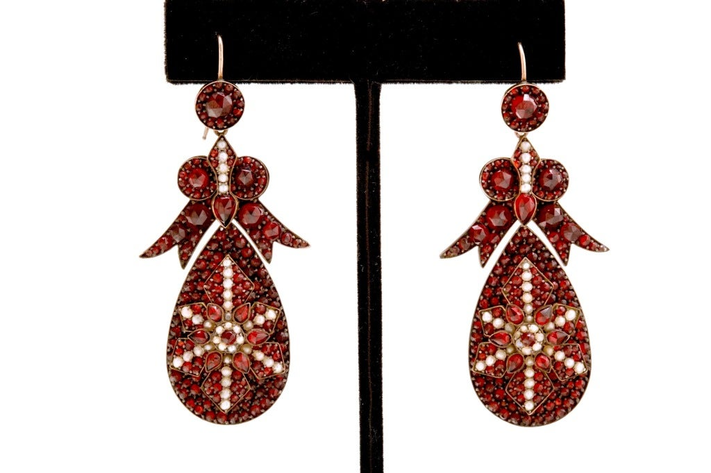 A spectacular pair of antique Bohemian Garnet and Seed Pearl encrusted earrings with large pendant drops surrmounted by beautiful bow form tops and gold wire backs, a truly grand and dramatic pair of earrings, unsigned. The length of the earring not