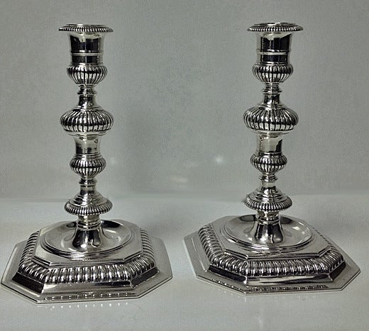 Pair of 17th century style cast candlesticks, London 1963, Carrington & Company. Each on octagonal raised fluted bases, fluted knopped stems and candle socket. Height: 6 ½ inches. Weight: 813.54 grams.