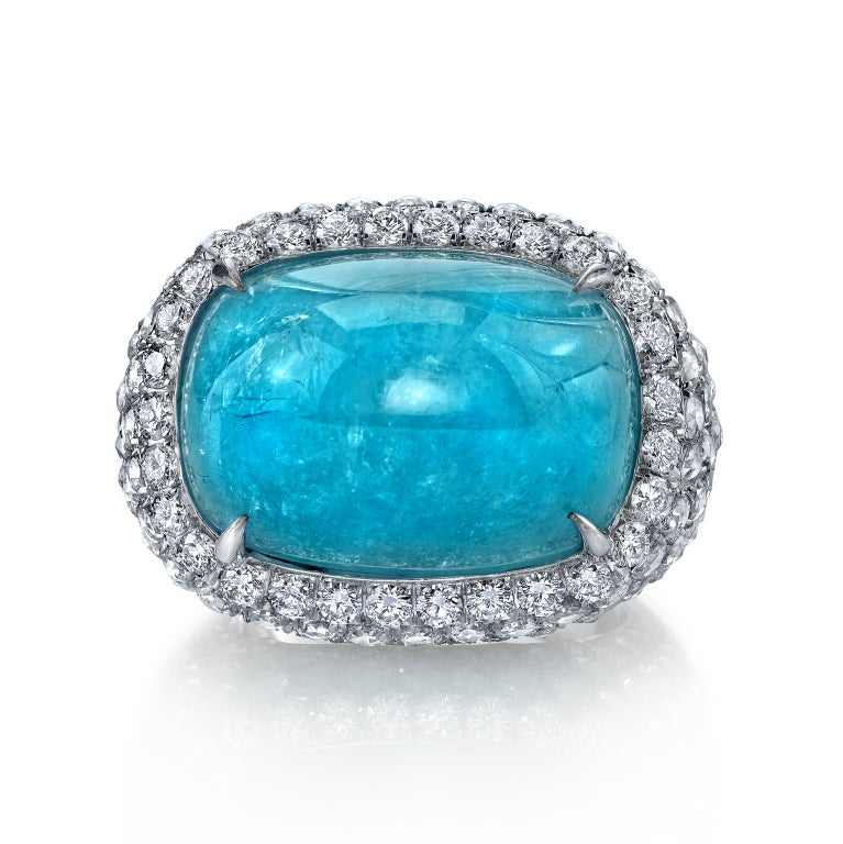 A rare and ultra exclusive 28.98ct cushion Paraiba Tourmaline cabochon, set in a luxuriously hand crafted platinum ring, accented by 3.46ct total of rose cut diamonds and 0.72ct total of round brilliant diamonds. 