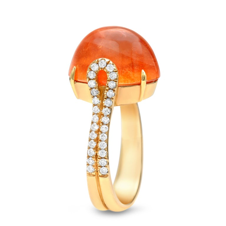 A 12.82ct bright and intense orange Mandarin Garnet cabochon, showcased in an 18K yellow gold ring with a total of 0.39ct diamonds. Signed by Tamir.