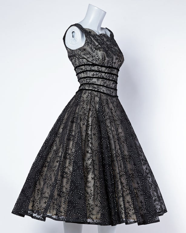 The 1950's at their best!-- Stunning nude, black and white full circle party dress in sheer burnout velvet organza. Scalloped bustline and nude lining. Shelf bust and flattering ringed bodice to accentuate that tiny waist. Rear zip closure.