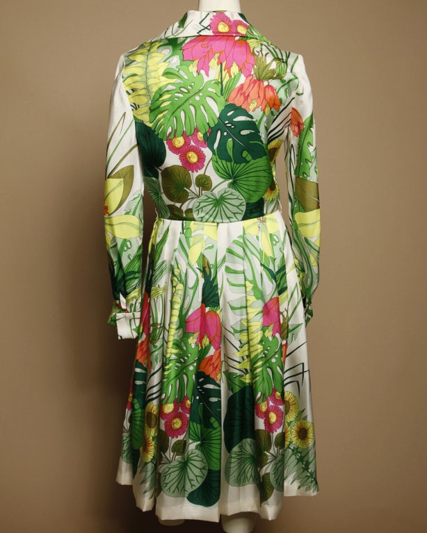 Kiki Hart designed upscale garments during the 1960's. Her New York based design house was known for superior craftsmanship and expensive fabrics. This creamy silk dress by the designer has the most vibrant tropical botanical print. This dress seems