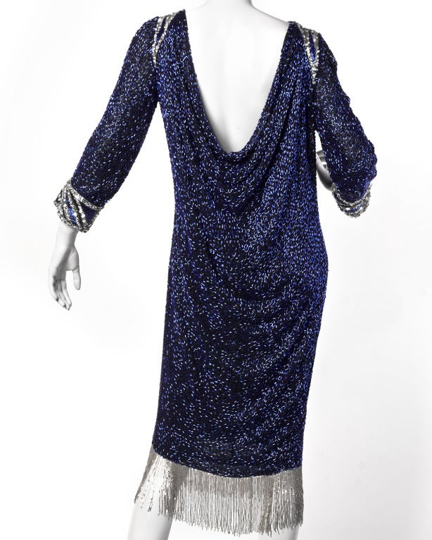 Stunning cobalt blue glass beaded cocktail dress by Bob Mackie. This heavily beaded and sequin embellished formal features silver Art Deco inspired keyhole collar and arm cuffs, a plunging draped two-layer back, and swinging silver beaded fringe
