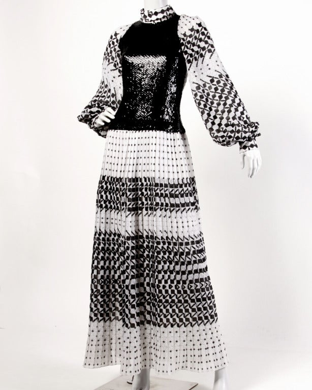 Iconic 1970's black and white graphic printed maxi dress with a clear sequin overlay bodice, pleated skirt and full poet sleeves. Drop waistline leaves room to pair with your favorite belt or wear it as is. The dress is fully lined and features rear