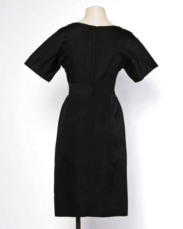 The perfect little black dress! Tiny nipped waist, V-neckline, and nude illusion peek-a-boo lace accents on the bodice. Short sleeves and hourglass silhouette. Rear metal zip closure.  DETAILS:  Unlined Back metal zip closure Circa: