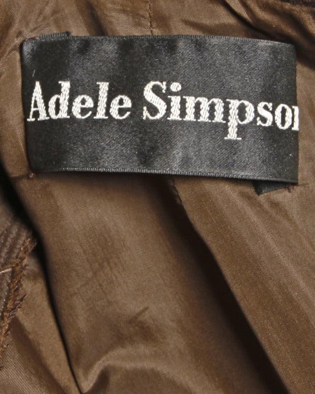 Chocolate brown crepe long sleeved dress with a striped ascot bow tie at the neck by designer Adele Simpson. Rear zip closure. Partially lined.  DETAILS:  Partially lined Back zip closure Circa: 1970s Label: Adele Simpson Estimated Size: