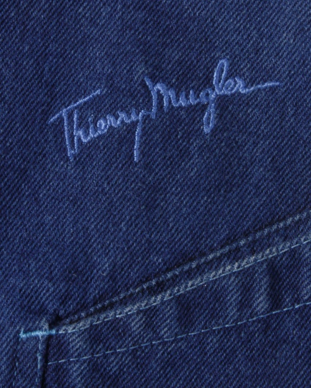 Dark denim jean skirt by Thierry Mugler. Snap front closure and embroidered logo on the back of the skirt.