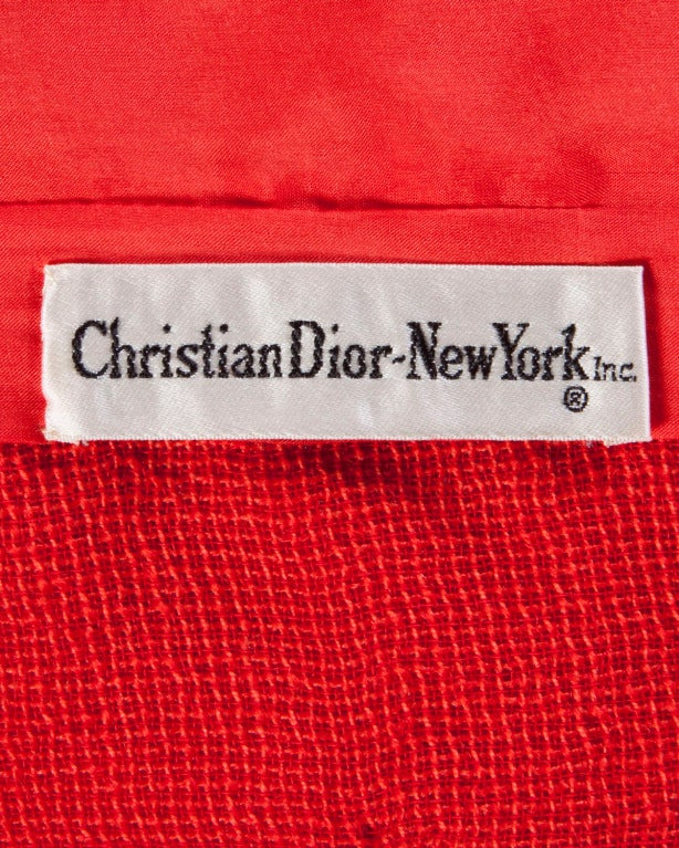 Stunning red-orange woven 3-piece suit set by Christian Dior for Saks Fifth Avenue circa 1960's. The three pieces can be worn together or separately and are all perfectly tailored.  The jacket is lined and features front frog closure. The skirt