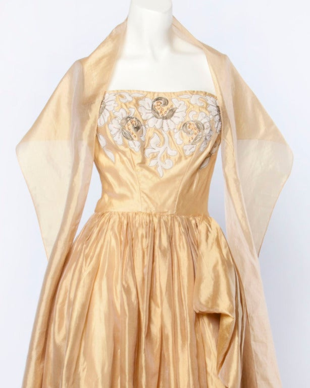 Stunning vintage gold silk gown from the 1950's by Kay Selig. The strapless bodice is hand-embroidered with floral appliques and pearl beading. The long silk skirt featured gathering on one side and a very full sweep with yards and yards of silk