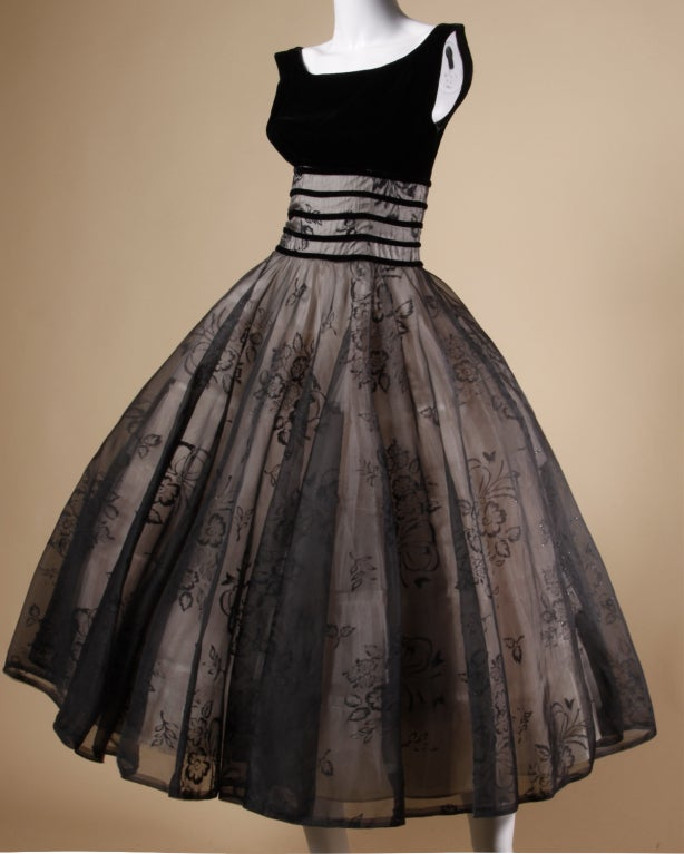 Chic 1950's black velvet and black burnout sheer organza party dress with a huge sweep, and built in crinoline. Shelf bust and 1950's classic silhouette. The burnout floral design features flecks of multicolor metallic glitter. Rear metal zip
