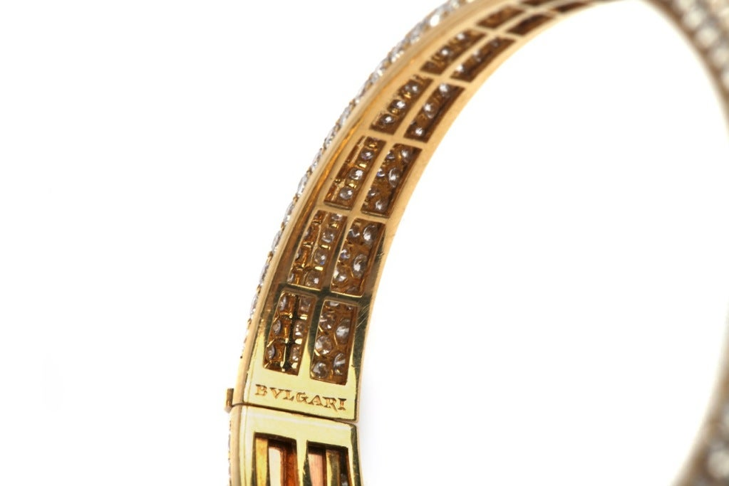 A bangle bracelet manufactured by Bulgari during the 1970s, presenting approximately 25 carats of quality cabochon emeralds and 18 carats of brilliant and baguette cut diamonds, on a fine 18kt yellow gold mounting.
