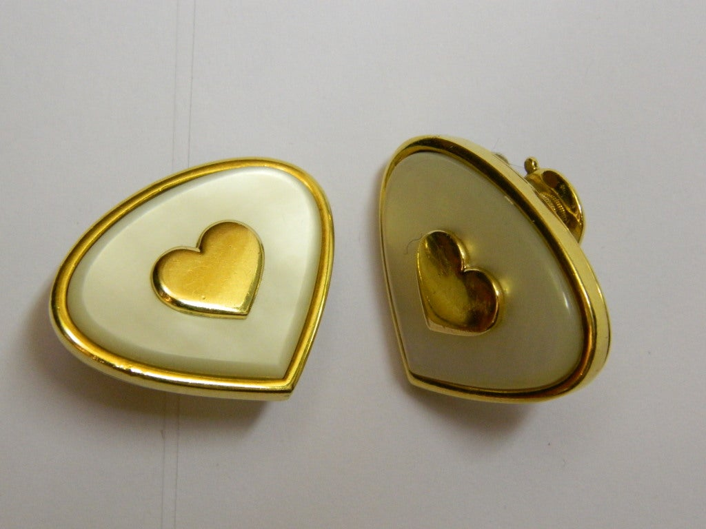 A pair of sophisticated earrings manufactured in France by Marina B during the 1980s, presenting mother of pearl decorations on an 18kt yellow gold mounting, centering a heart shaped gold element.