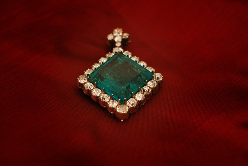 An extraordinary antique pendant of prestigious provenance (refer to certificate in pictures), manufactured in the first half of the 19th century, presenting a unique Colombian emerald weighing 87.50 cts, sided by old mine cut diamonds weighing a
