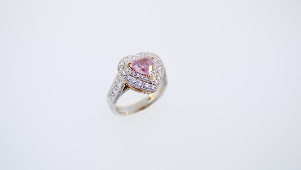 Platinum and 18K Pink Gold. 1.31 Carat Natural Fancy Intense Purple Pink Modern Heart Shape Brilliant cut Diamond, SI2 Clarity.  Total Weight in Diamonds is 3.01 Carats.