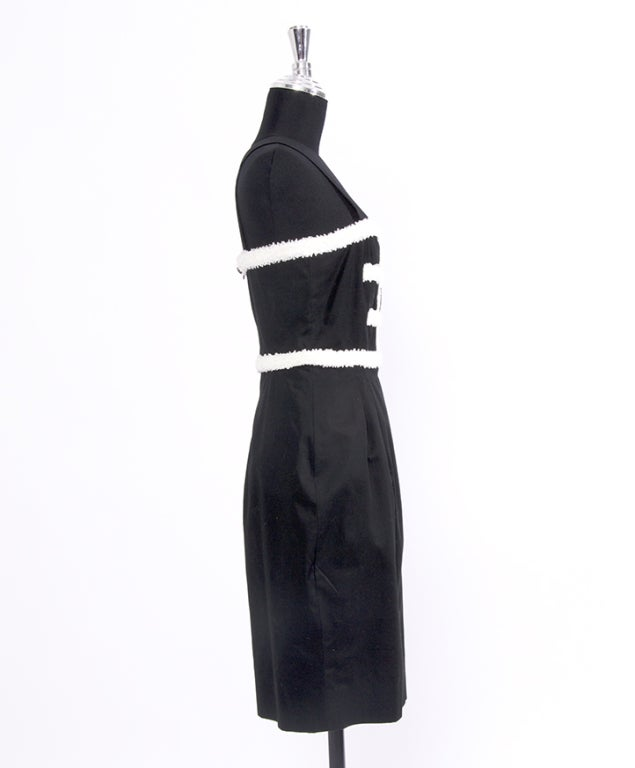 "Light knee-length dress in black with white ruche details and tulip skirt. Label says ""Chanel Boutique""."