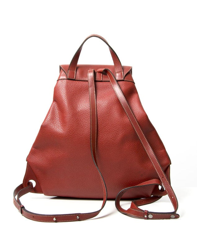 Fun and original leather backpack in brick red color by Deux de Delvaux. This practical bag has a grained leather body and a smooth flap. Dark silver hardware throughout. 