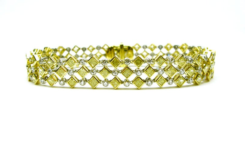 Uniquely designed handmade 18kt yellow gold and platinum bracelet. This one-of-a kind piece features 78 bezel set fancy yellow princess cut diamonds totaling 7.25cts and 78 bezel set white round brilliants totaling 3.90cts. This beautiful bracelet