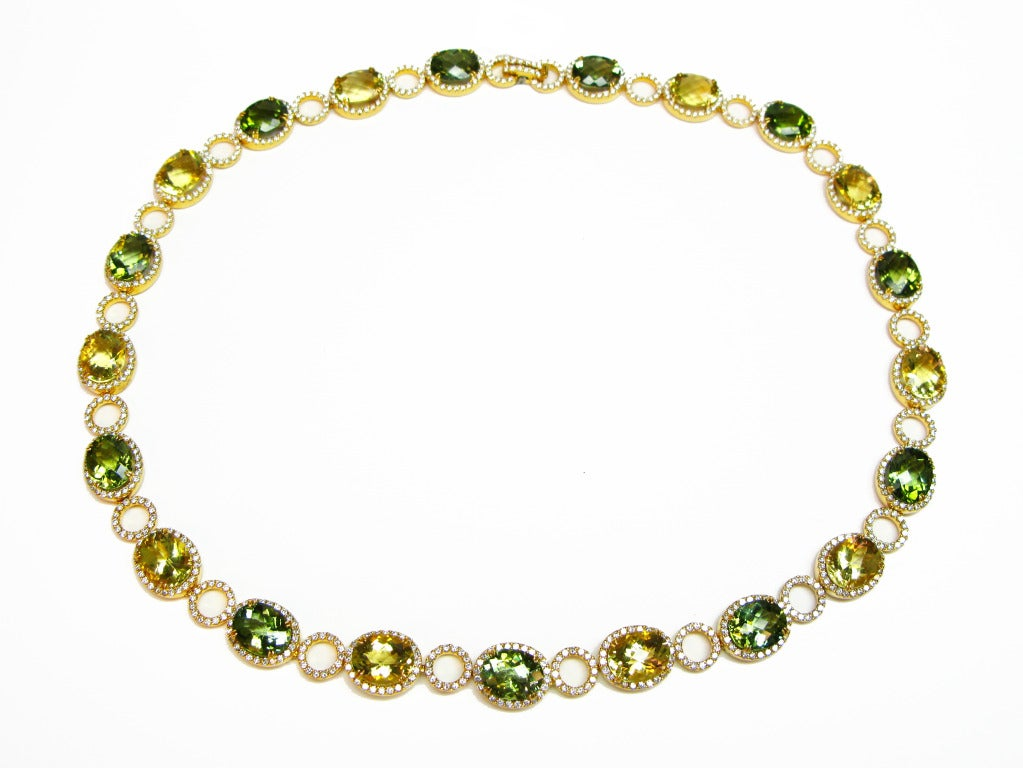 This stunning citrus inspired necklace, set in 18k yellow gold, features oval cut lemon quartz and green tourmaline stones, accented with diamond pave circular links. The color combination in this piece is absolutely striking! This knockout is