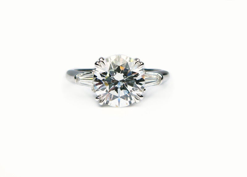 This exquisite 2.34ct F color VS1 clarity round brilliant diamond is set in a Harry Winston signed platinum band with tapered baguette side stones. This ring is pure perfection and will make any woman sparkle.