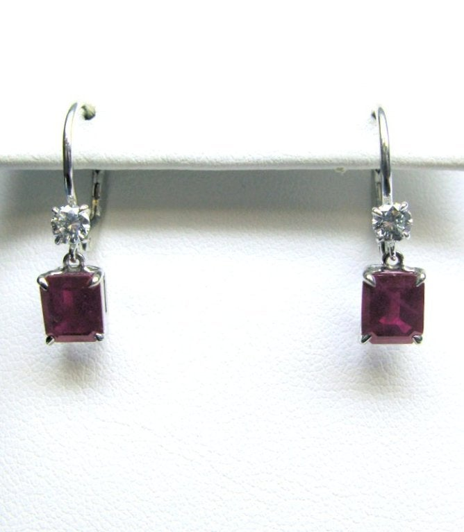 These classic 18kt white gold leverback earrings feature two richly colored red step-cut ruby drops weighing 2.48cts and two sparkling round brilliant diamonds weighing 0.28cts. These beautiful earrings can easily be worn from day to night and with