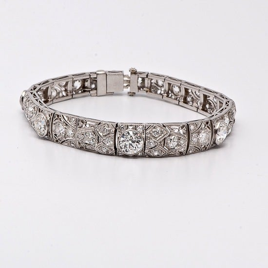 This platinum antique Art Deco bracelet is bezel-set with 9 European-cut diamonds. The three middle European-cut diamonds weighing an estimated 4.50cts in total. There are 2 intermediate size diamonds weighing an estimated 1.90ct total, and 4