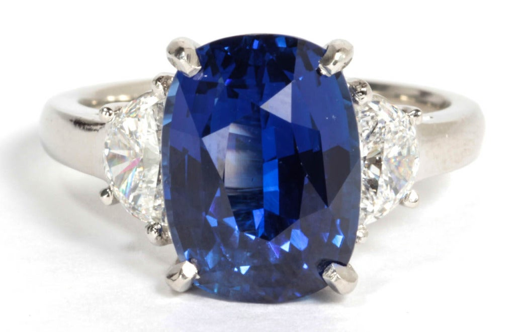 Certified natural no heat 6.09 carat Cushion cut sapphire set in handmade platinum and diamond mounting. .66 carats of diamonds.   This sapphire has exceptional color and brilliance.   The certificate states the color as VIVID BLUE and CORNFLOWER