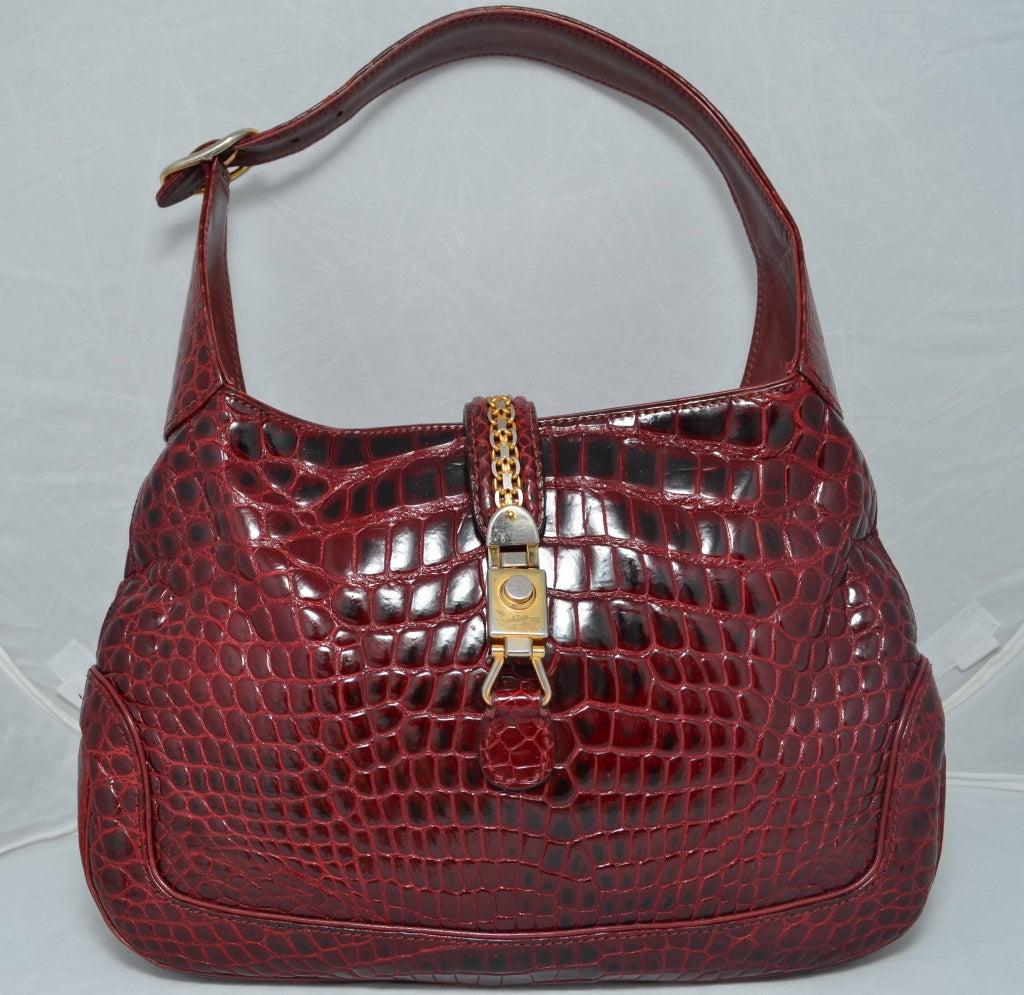 8d0134657 Gucci 1970's maroon crocodile Jackie O handbag with gold hardware. Push  button clasp closure.