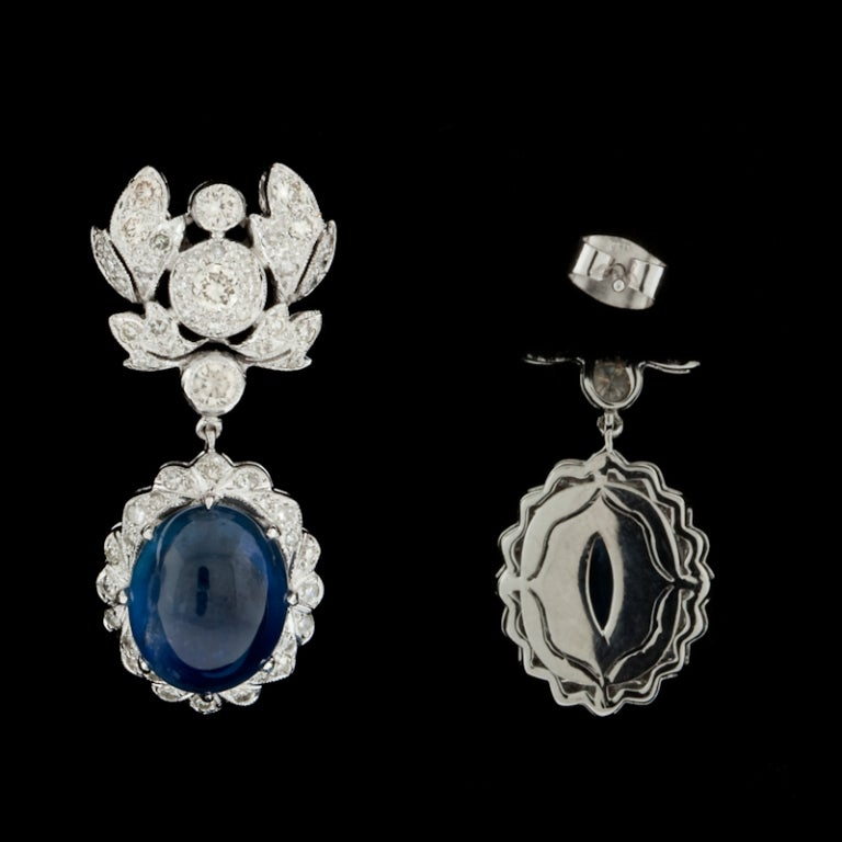 18Kt White Gold Sapphire & Diamond Earrings feature 2 Oval Cabochon Sapphires for a total approximate weight of 13cts and 112 Round Brilliant Cut Diamonds for approximately 1.45cts.  Earrings measure 12mm wide x 30mm long and weigh 12.8 grams.