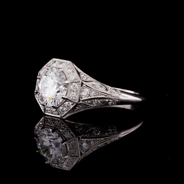 Custom made ring featuring a 1.52ct Round Brilliant Cut diamond, complete with GIA Grading Report for the center stone, accented by an octagonal pave diamond border and diamond accented floral motif platinum ring, mounted with 8 prongs. The round