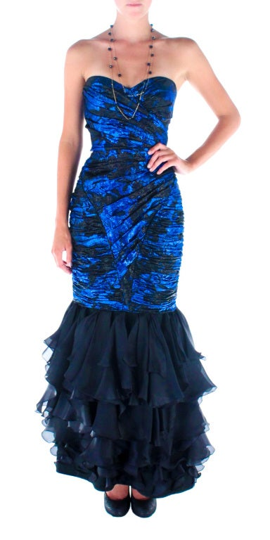 Beautiful Ungaro mermaid gown in black and cobalt silk lamé.  Inspired by the finest 1950's French tradition, it has a fully boned corset and layers of bias cut ruffles to the floor. Size: SMALL Bust: 32