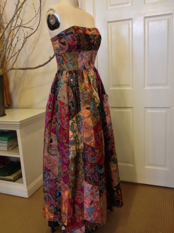 """Oscar de la Renta took """"boho-chic"""" to a whole new level when he created this strapless gown.  Gorgeous silk in pinks, oranges, purples and greens are patched together with crushed velvet placed sporadically for added texture.  Intricate embroidery"""
