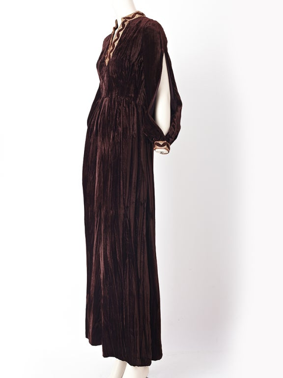 Oscar de la Renta, rich chocolate crushed velvet, maxi dress with a gold and velvet trim along neckline and cuffs. Front slit. Long full sleeves with open slits going from cuff to shoulder.
