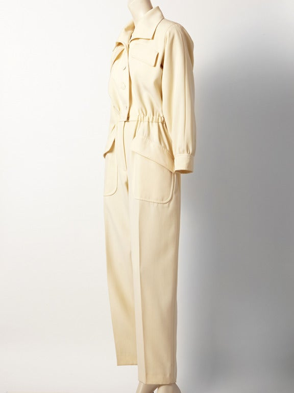 Yves Saint Laurent, ivory, wool gaberdine, jumpsuit. Trouser has large patch pockets with flaps, bodice has breast pockets and a pointed collar. Waist is elastic. C. 1980's.
