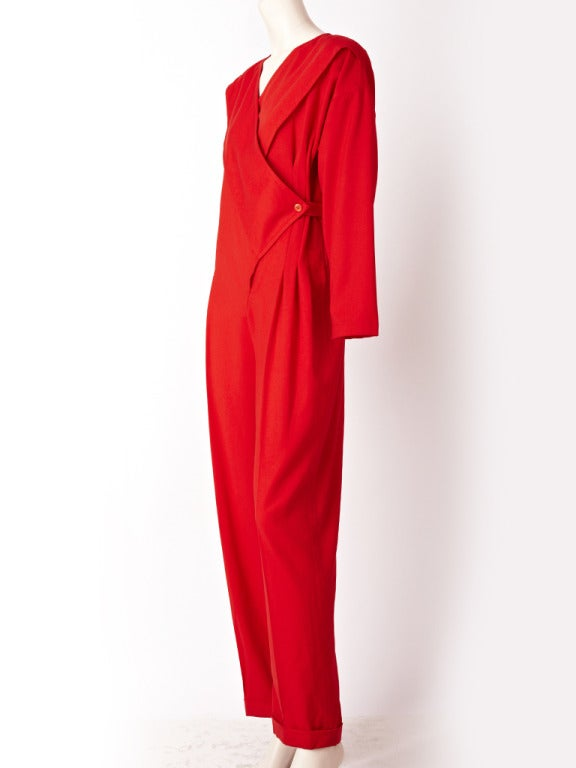 "Ronaldus Shamask, Chinese red, wool gaberdine, trouser jumpsuit. Open ""v"" neckline with a wrap style bodice. Self belt wraps around the back of the jumpsuit and fastens at the left side defining the waist."