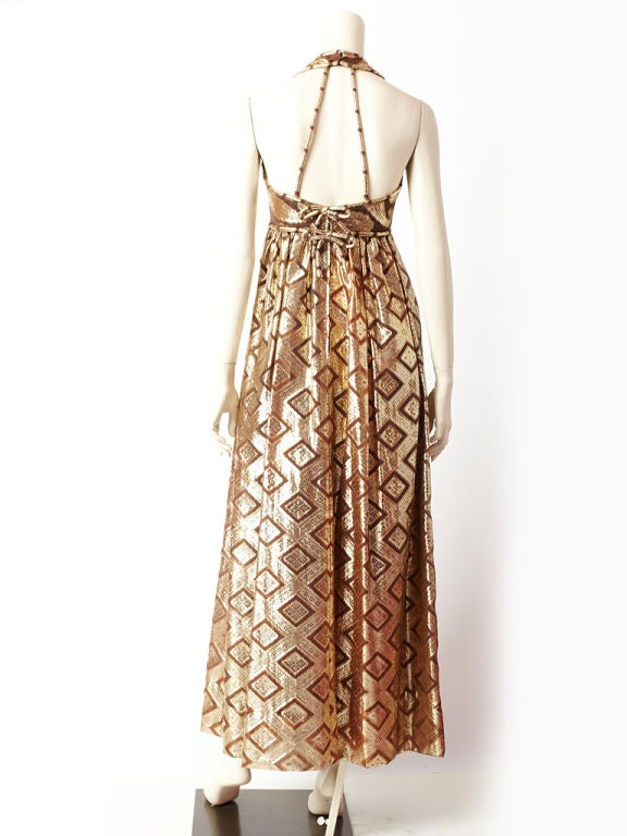 Saks Fifth Ave., halter neck, empire waist, gold lame and bronze toned long dress. Dress bodice has a paisley pattern and skirt has a different geometric complimenting pattern. Back is open with straps that anchor the dress on the body. There are