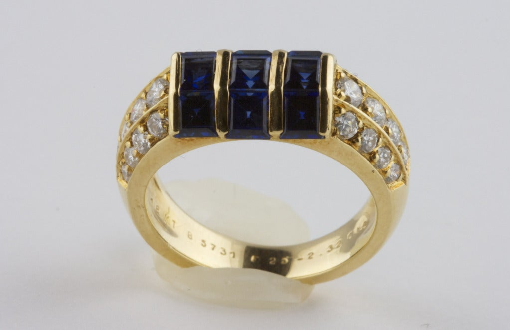 The Van Cleef & Arpels ring is in 18k yellow gold set with 9 square cut sapphires of excellent quality that weigh 2.32 carats. The sapphires are accented by 24 round brilliant cut diamonds that are all colorless, clean, and beautifully
