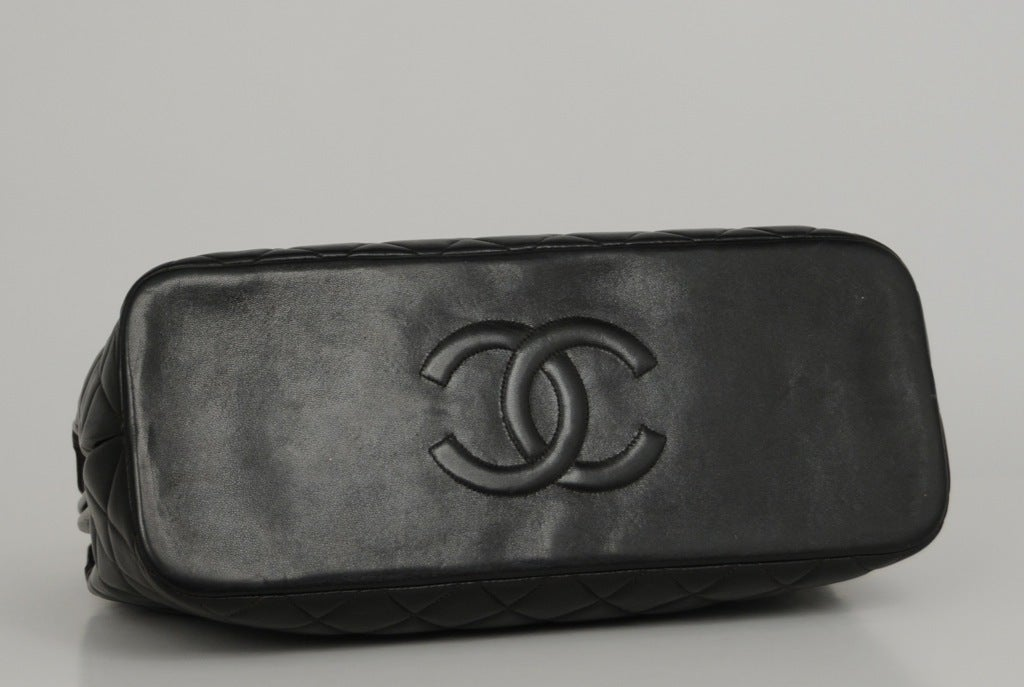 Large black quilted doctor bag with CC mademoiselle closure. Double leather and chain strap with stitched CC on bottom.