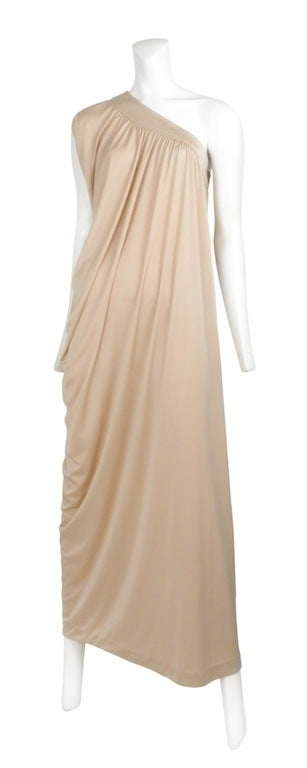 Champagne color asymmetrical jersey gown, with zip side closure and beautiful draping detail that falls to one side.