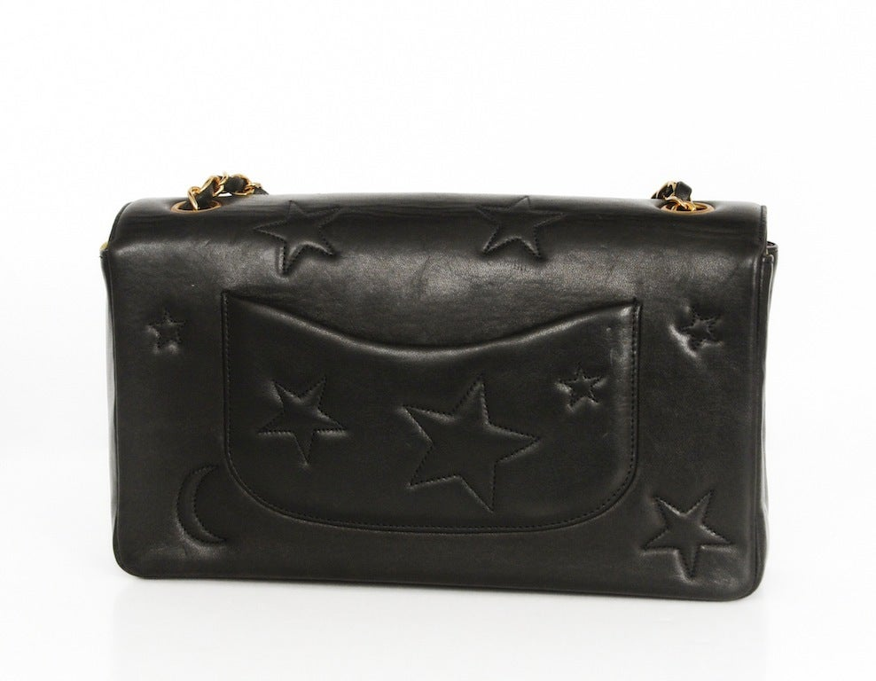 Black lambskin shoulder bag with cosmic stars and moon beam stitching throughout.  CC mademoiselle closure at front and large patch pocket at back. Single leather and chain strap. Dust bag and hologram in tact.