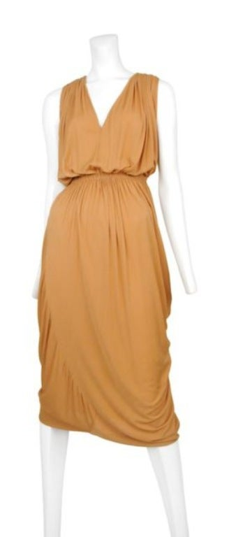 Beautiful Pale peach jersey Grecian style gown. A large hook and eye closure secures the waistline creating an hourglass silhouette from the front and cape like draping from the back. Undeniably 1970's Halston!