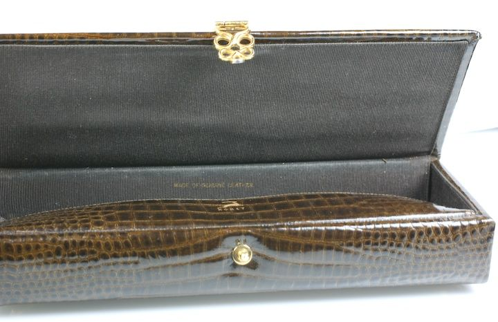 Leather clutch by Koret designed to resemble a Victorian glove box. The leather is embossed to look like shiny alligator with loopy gilt mounts. Very chic and unusual. Lined in black faille.<br />