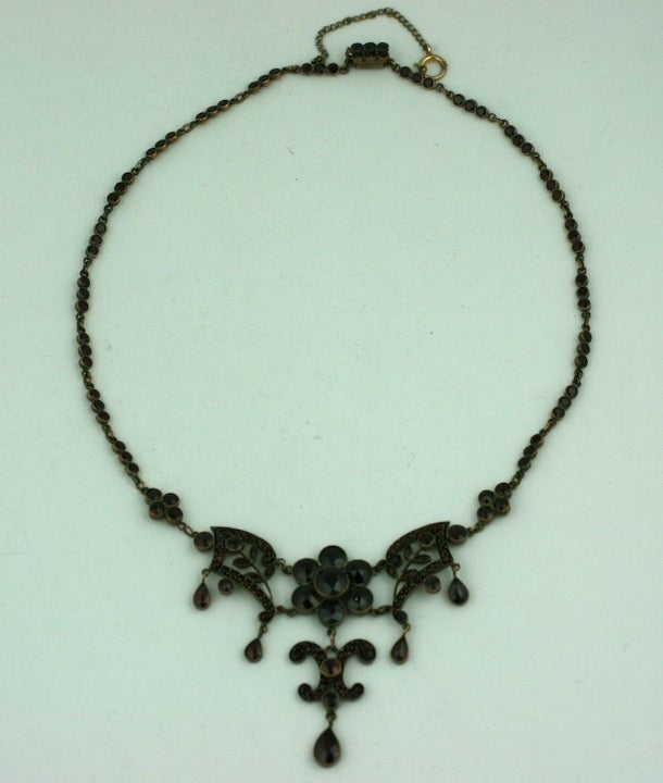 Attractive garnet set necklace with articulated fern patterned links and drops. Larger stones and drops have rose cut stones.  The links are bezel set with tiny garnets as well.