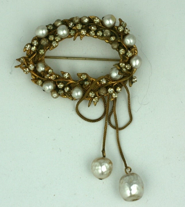 Attractive Miriam Haskell oval wreath form brooch of pastes and faux pearls in signature Russian gold settings. A pair of pearl pendants hang from gilt fox chaining. 2.5