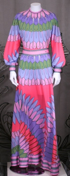 Charming and striking print dress by Artemis from the 1970s. Brightly hued floral petals are perfectly placed so they emanate from the neckline and waist and hem. Full gathered sleeves and back zip entry. Size 4-6, USA 1970s. Excellent