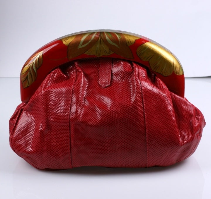 Unusual red snake clutch with handpainted gilt floral wood frame. Signed