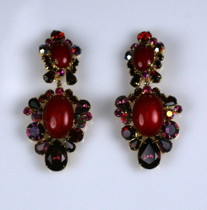 Early K.J.L earring from the late 1960's with tonal rhinestones in iridescent ruby, amythest surrounding a unusual enamel cabochon. Clip back fittings. 1960's USA. 3.25