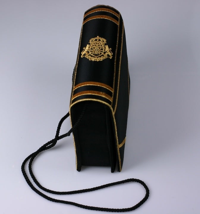 """Charming figural """"book"""" bag in black satin with embroidered crest and detailing. Flap opens in front with magnetic closure and bag hangs from twisted cord strap. 1980s USA. 7.5"""" x 7""""h x 2"""", strap 40"""". Excellent condition."""