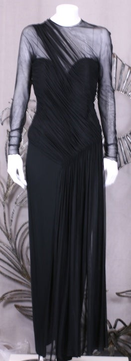 Vicky Tiel's chic and sexy draped stretch illusion gown on a matte jersey base. The illusion is ruched at shoulder and is gathered across bodice and releases to a gathered panel which floats over a doubled matte jersey gown with front slit. Bodice
