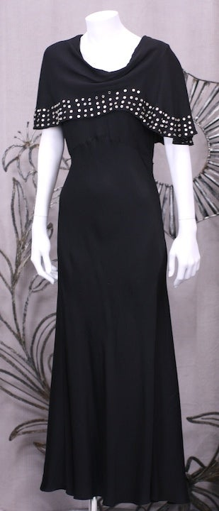Unusual gown from the 1930's with metal stud detailing. A precursor of punk style, the detailing on this rayon crepe gown is as innovative as the off kilter side draped cowl neckline.  Gowns from the period like these which are incredibly modern