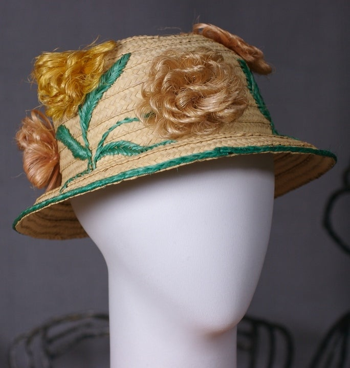 Fun straw hat decorated with silly floral blooms of pale raffia loops which almost look like tufts of hair. 